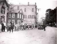 Parade Coming c. 1930....Greenwood Avenue near the south end of P.T. Barnum Square. The two wood frame buildings in the left of the photo were razed in the early 1960s and have been replaced by P.T. Barnum Plaza. The house, exhibiting the American flag, was home to a tailor shop operated by J.M. Thurner.